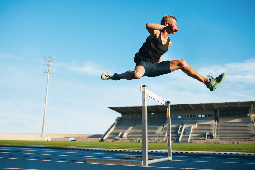 Professional male track and field athlete during obstacle race. Young athlete jumping over a hurdle during training on racetrack in athletics stadium.