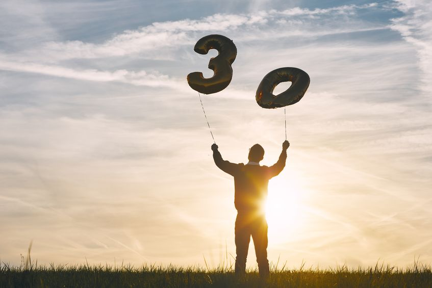 Man celebrates thirty years birthday. Person holding helium balloons in shape of number 30 at sunset.